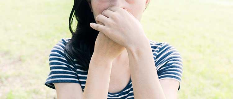 鼻をおさえている女性