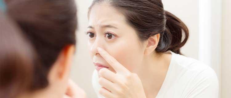 鏡で鼻を確認する女性