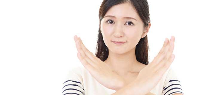 手をバッテンしている女性の画像