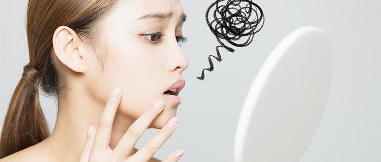 鏡で肌を確認する女性