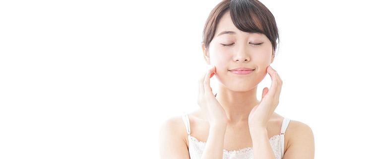ツルスベ肌の顔を両手で覆っている笑顔の女性の写真